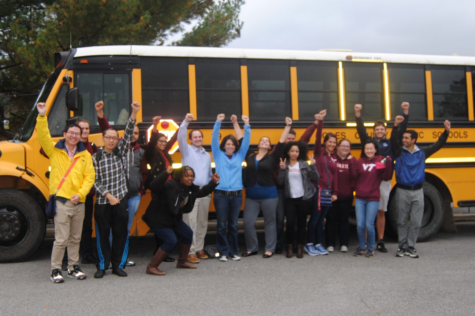 This photo shows 16 young adults posing with a yellow school bus behind them. Their arms are raised over their heads and they are smiling.