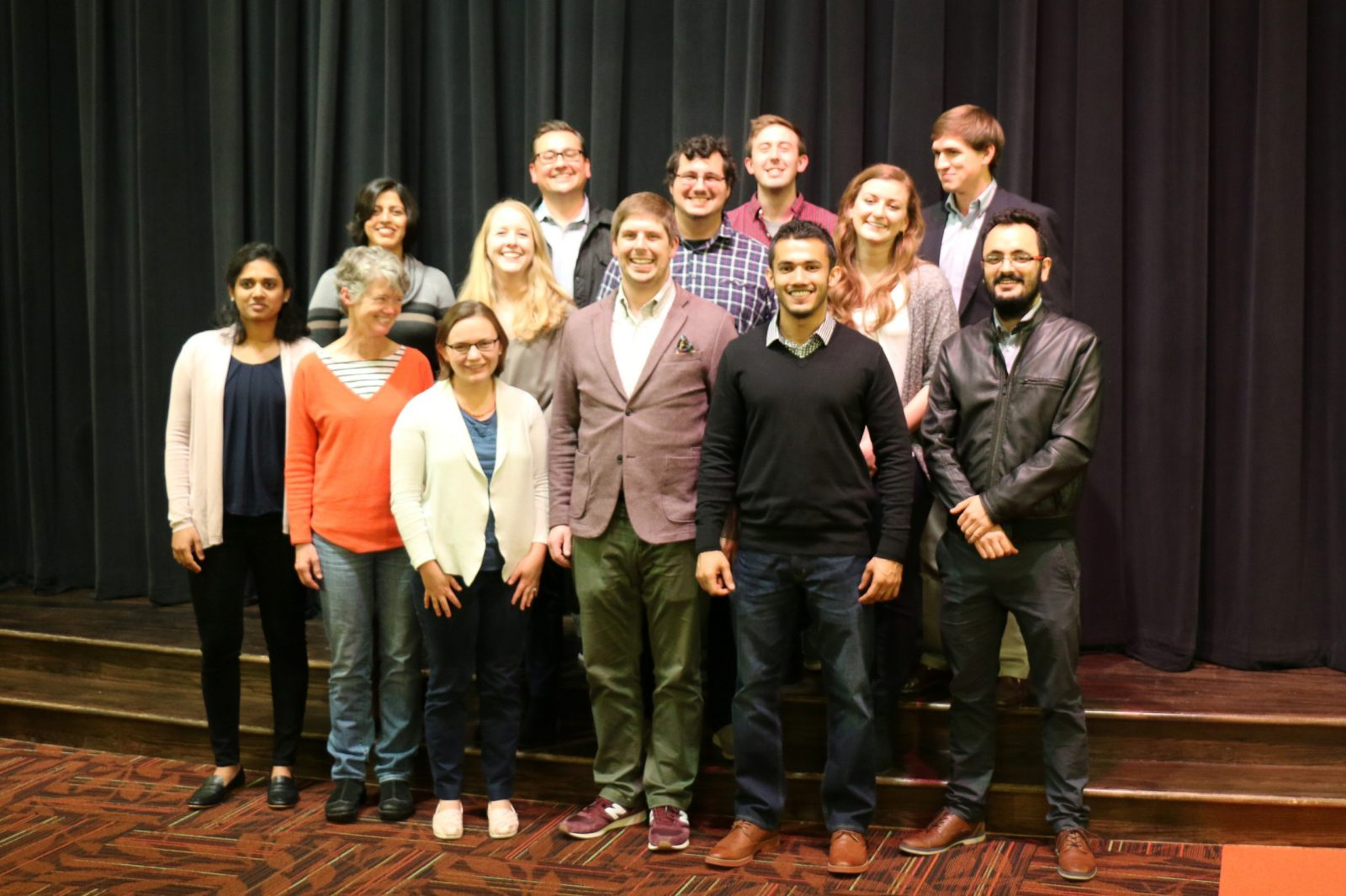 This photo shows 13 people posed for a group photo with a black stage curtain behind them. All are smiling. The group is made up of males and females and is of mixed ethnicities or nationalities.