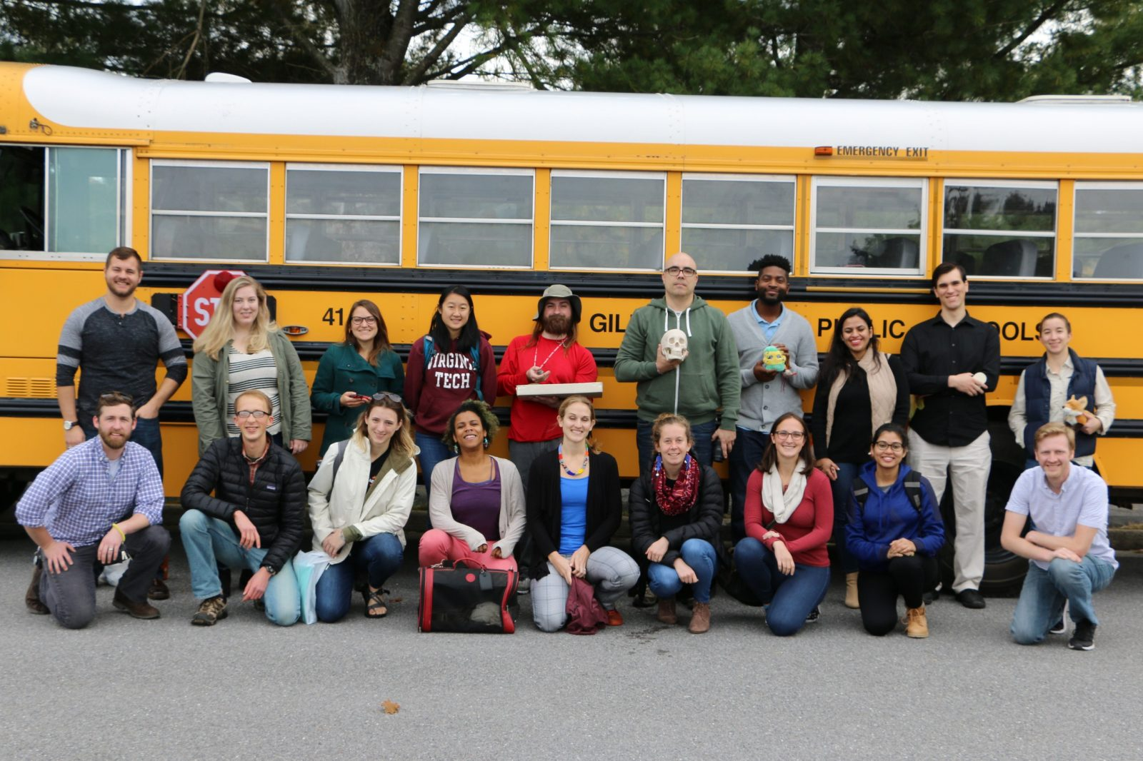 This photo shows 9 young adults squatting or crouching and another 10 people standing behind them. Behind the entire group in the long side of a yellow school bus. The group is racially and ethnically diverse and made up of both males and females.
