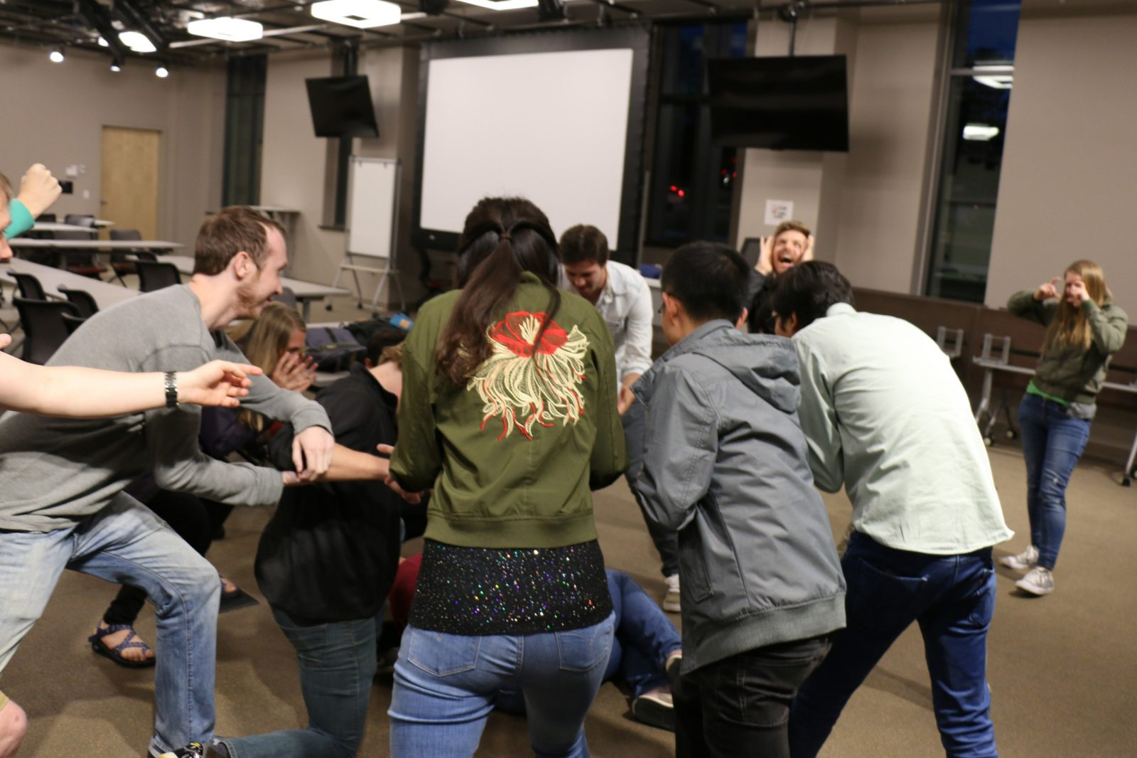 This photo shows at least 10 people in a classroom, several of whom are in a circle pointing at someone on the floor. Another is in the right background holding a pretend camera to her face.